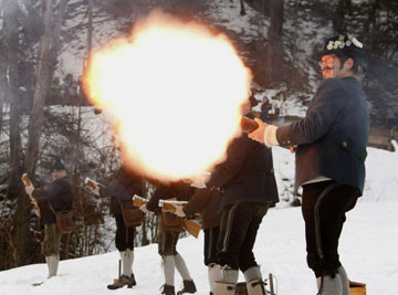 Traditionally dressed Alpine mountaineers fire salut to start the annual sledge race in Garmisch-Partenkirchen