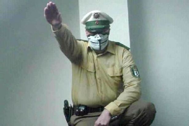A man in a police uniform pulls up his right arm in a Hitler salute
